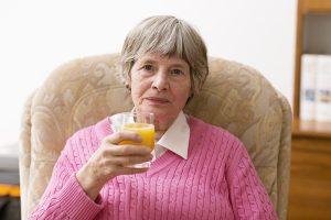 82 year old senior woman drinking orange juice at home