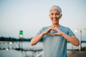 Active senior woman making a heart with her hands