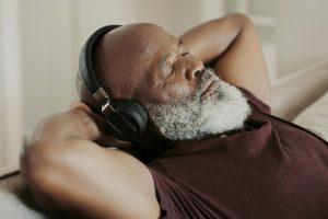 senior man relaxing listening to headphones