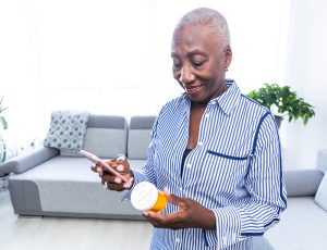 Senior woman holding pills and reading the information on the label