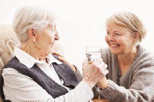 caregiver handing glass of water to senior
