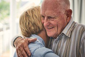 elder man hugging family caregiver