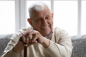 happy senior man leaning on cane