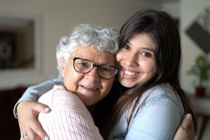 senior Latino woman with dementia hugging caregiver